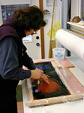 Nancy Current siliconing glass in her studio.